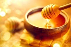 Honing Gezonde organische dikke honing die van honingsdipper druipen in houten kom Zoet dessert royalty-vrije stock afbeelding