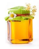 Honing in glaskruik met bloemen stock afbeeldingen