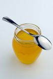 Honing in glaskruik met lepel op bovenkant royalty-vrije stock afbeelding