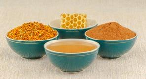 Honing, honingraat, stuifmeel en kaneel in kommen royalty-vrije stock foto's