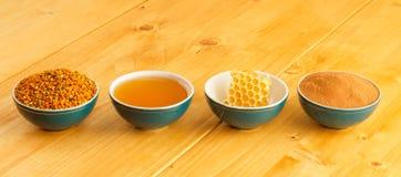 Honing, honingraat, stuifmeel en kaneel in kommen royalty-vrije stock afbeeldingen