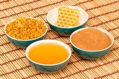 Honing, honingraat, stuifmeel en kaneel in kommen Stock Foto's
