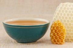 Honing in kom met honingraat stock foto