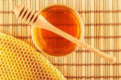 Honing in kruik met dipper en honingraat op mat royalty-vrije stock afbeelding