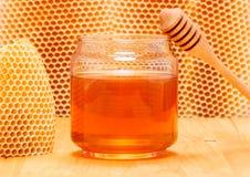 Honing in kruik met dipper op honingraatachtergrond royalty-vrije stock afbeeldingen