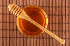 Honing in kruik met dipper op mat Royalty-vrije Stock Afbeelding