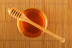 Honing in kruik met dipper op mat Royalty-vrije Stock Afbeeldingen