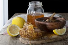 Honing in kruik met honingraat en houten drizzler royalty-vrije stock afbeeldingen