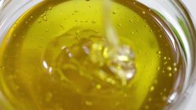 Honing in kruik op witte achtergrond wordt gegoten die stock footage