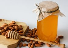 Honing met amandelen en hoheylepel Stock Foto's
