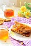 Honing op toost wordt gegoten - ontbijt dat Stock Afbeeldingen