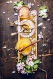 Honing, thee en de lentebloesem op honingraat, donkere houten achtergrond Stock Fotografie