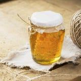 Honingraat in een glaskruik op rustieke houten achtergrond royalty-vrije stock foto's