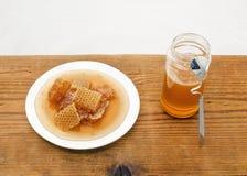 Honingraat en Honey Jar op Houten Lijst stock afbeeldingen