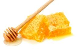Honingraat met honingsdipper en honing op witte achtergrond wordt geïsoleerd die royalty-vrije stock foto's