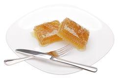 Honingraat op witte plaat royalty-vrije stock afbeelding