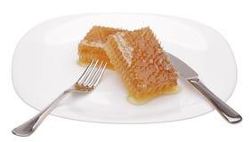 Honingraat op witte plaat stock afbeeldingen