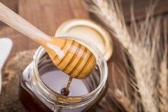Honingsdipper in een kruik, op een oude uitstekende houten achtergrond - sluit stock afbeelding