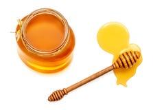 Honingsdipper en honing in kruik op witte achtergrond wordt geïsoleerd die Natu stock afbeeldingen