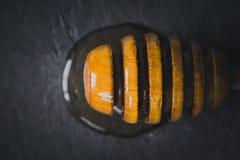 Honingsdipper op de donkere steen hoogste mening als achtergrond Royalty-vrije Stock Afbeelding