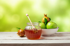Honingskruik en verse appelen met granaatappel over groene bokehachtergrond Stock Afbeeldingen