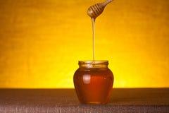 Honingskruik met dipper en stromende honing stock afbeelding