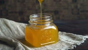 Honingskruik met dripper Honingskom op lijst Honing die in fles druipen stock video