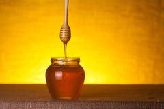 Honingskruik met houten dipper en stromende honing stock fotografie