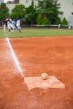 Honkbal en basis op honkbalveld met spelers het praktizeren stock afbeelding