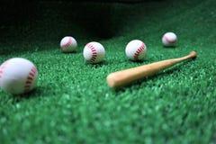 Honkbal en knuppel op het groene gras met exemplaarruimte stock foto's
