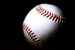 Honkbal tegen donkere achtergrond   Stock Afbeelding