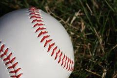 Honkbal tegen natuurlijk gras Stock Fotografie