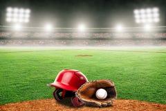 Honkbalhandschoen, Bal, en Helm op Gebied in Openluchtstadion met Exemplaarruimte stock foto