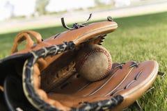 Honkbalhandschoen en Bal op Gebied stock foto's