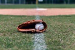 Honkbalhandschoen en bal op vuile lijn stock foto