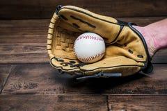 Honkbalhandschoen op zijn hand met de bal Stock Foto