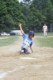 Honkbalspeler die in basis, Weinig Ligaspel, Hebron, CT glijden Stock Foto's