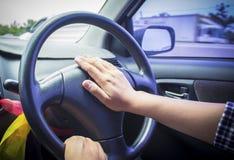 Honking the horn. In a car stock photos
