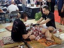 Lady lays on floor as she gets tattoo. Honolulu - August 6, 2017: Lady lays on floor as she gets tradition Hawaiian tattoo from two men at the Hawaii Tattoo Expo royalty free stock images