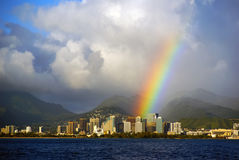 Honolulu Hawaii with a bright rainbow after a rain stom seen fro. M the open ocean on Oahu island Stock Photo