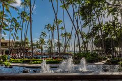 Honolulu, Hawaii- Dec. 13, 2018: View from Hilton Hawaiian Village's main lobby of a fountain, palm trees and pool royalty free stock photo
