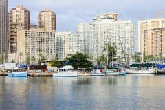 Honolulu, Hawaii, USA - May 30, 2016: Yachts docked at Ala Wai Boat Harbor. In the Kahanamoku Lagoon against cityscape of Ala Moana stock photography