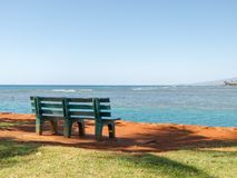 Honolulu Park Bench. Lonely park bench overlooking the ocean on the beach Stock Images