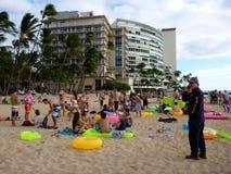 Honolulu Police officer calls for backup as he inspects beach pa. HONOLULU, HI - JANUARY 21: Honolulu Police officer calls for backup as he inspects beach party Royalty Free Stock Photography