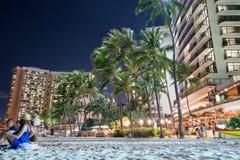 HONOLULU USA - AUGUSTI, 14 2014 - folk som har gyckel på natten på den sandiga stranden för waikiki Royaltyfri Fotografi
