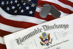 Honorable discharge paper on flag. Military discharge certificate and dog tags on an American flag Royalty Free Stock Photography
