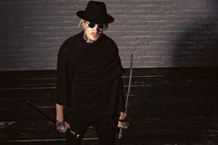 Honor and dignity. Warrior in black sunglasses, hat and clothes, top view. Samurai, buddhist concept. Man with swords standing on wooden floor. Harakiri royalty free stock image