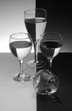 Honor guard. Three glasses standing guard on their fallen comrade on black and white background stock images