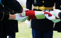 Honor Guard and Flag. Honor Guard at Arlington National Cemetery folding flag over casket with gravestons in the background Stock Image