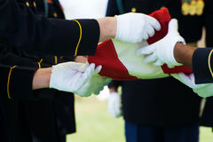 Honor Guard and Flag. Honor Guard at Arlington National Cemetery folding flag over casket with gravestons in the background Royalty Free Stock Photos